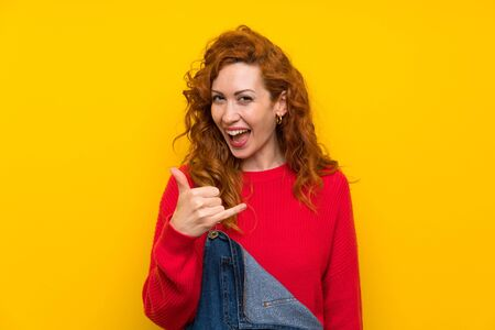 Redhead woman with overalls over isolated yellow wall making phone gesture
