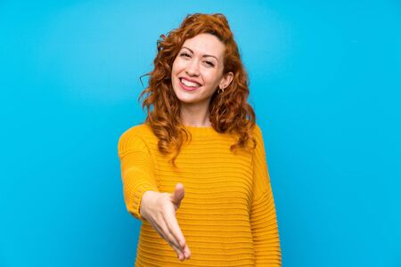 Redhead woman with yellow sweater shaking hands for closing a good deal