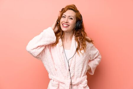 Redhead woman in dressing gown listening music