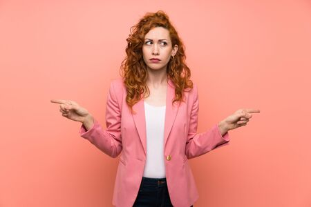 Redhead woman in suit over isolated pink wall pointing to the laterals having doubts