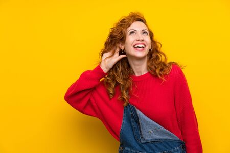 Redhead woman with overalls over isolated yellow wall listening something Imagens