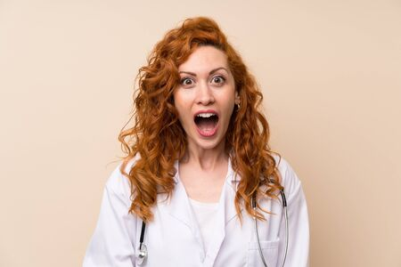 Redhead doctor woman with surprise facial expression Imagens