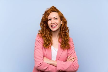 Redhead woman in suit over isolated blue wall keeping the arms crossed in frontal position
