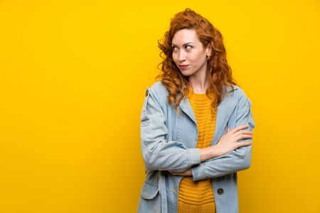 Redhead woman over isolated yellow background standing and thinking an idea