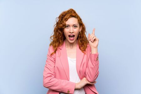 Redhead woman in suit over isolated blue wall thinking an idea pointing the finger up