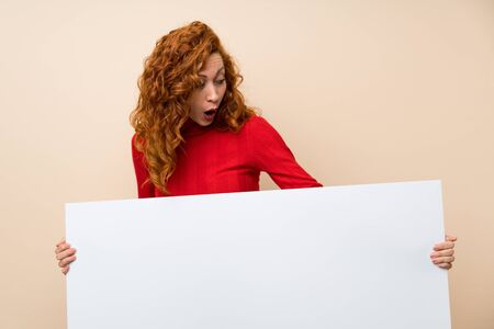 Redhead woman with turtleneck sweater holding an empty white placard for insert a concept Imagens