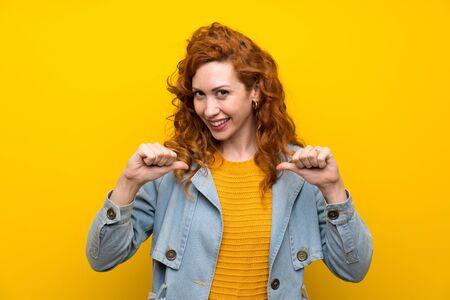 Redhead woman over isolated yellow background proud and self-satisfied