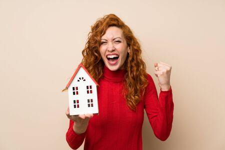 Redhead woman with turtleneck sweater holding a little house