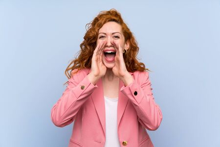 Redhead woman in suit over isolated blue wall shouting and announcing something