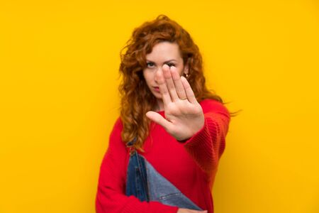 Redhead woman with overalls over isolated yellow wall making stop gesture with her hand