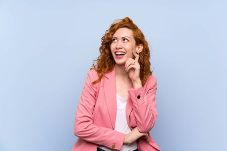 Redhead woman in suit over isolated blue wall thinking an idea while looking up