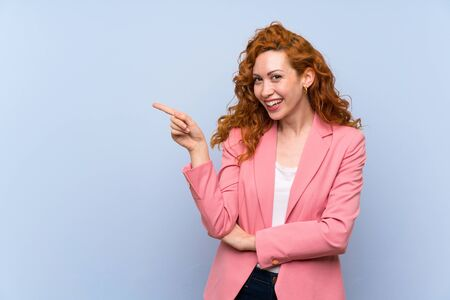 Redhead woman in suit over isolated blue wall pointing finger to the side