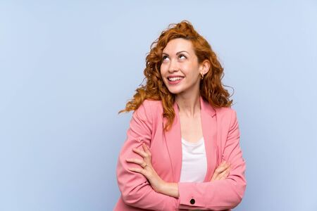 Redhead woman in suit over isolated blue wall looking up while smiling Imagens