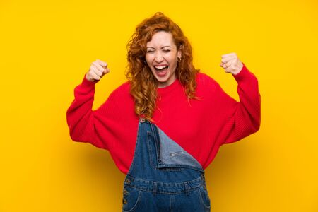 Redhead woman with overalls over isolated yellow wall celebrating a victory Imagens
