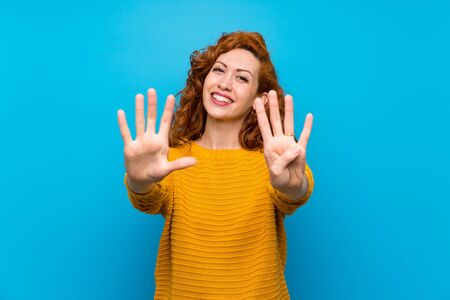 Redhead woman with yellow sweater counting nine with fingers