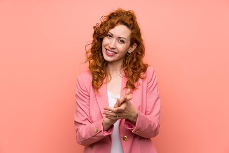 Redhead woman in suit over isolated pink wall applauding