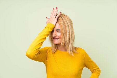 Young blonde woman over isolated green background having doubts with confuse face expression