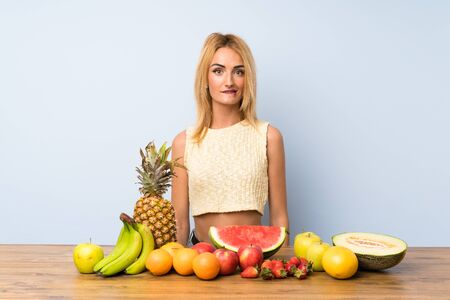 Young blonde woman with lots of fruits having doubts and with confuse face expression