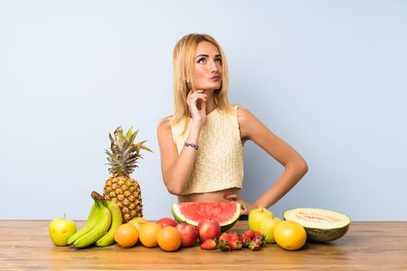 Young blonde woman with lots of fruits thinking an idea