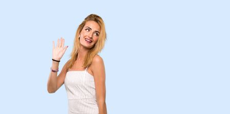 Young blonde woman saluting with hand with happy expression over isolated blue background