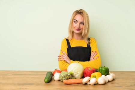 Young blonde woman with lots of vegetables thinking an idea