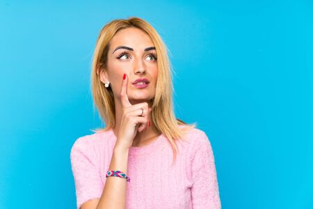 Young blonde woman over blue background thinking an idea 写真素材
