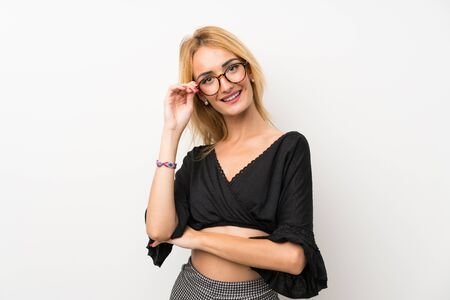 Young blonde woman over isolated white wall with glasses and happy