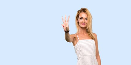 Young blonde woman happy and counting three with fingers over isolated blue background