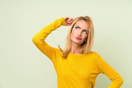 Young blonde woman over isolated green background having doubts and with confuse face expression