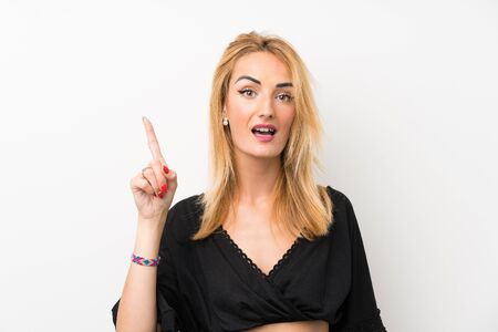 Young blonde woman over isolated white wall thinking an idea pointing the finger up