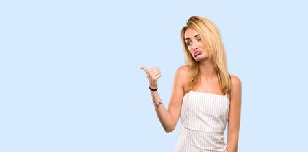 Young blonde woman unhappy and pointing to the side over isolated blue background