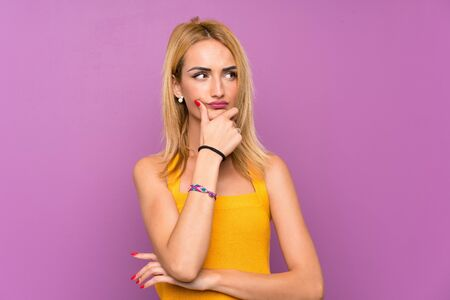 Young blonde woman over purple background thinking an idea