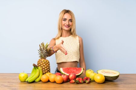 Young blonde woman with lots of fruits handshaking after good deal
