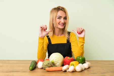 Young blonde woman with lots of vegetables proud and self-satisfied