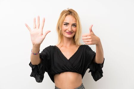 Young blonde woman over isolated white wall counting six with fingers