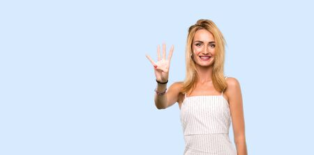 Young blonde woman happy and counting four with fingers over isolated blue background