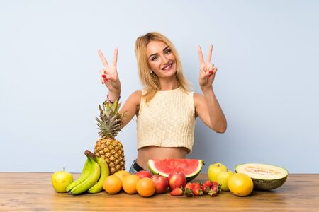 Young blonde woman with lots of fruits smiling and showing victory sign