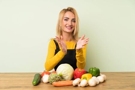 Young blonde woman with lots of vegetables applauding