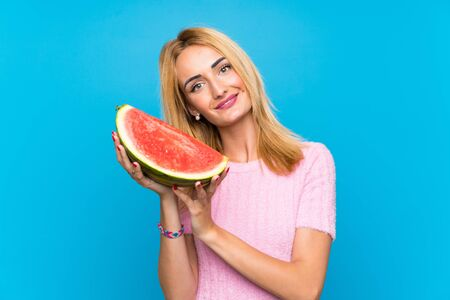 Young blonde woman holding fruits