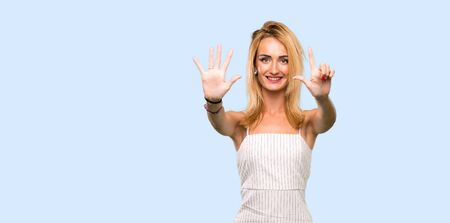 Young blonde woman counting seven with fingers over isolated blue background