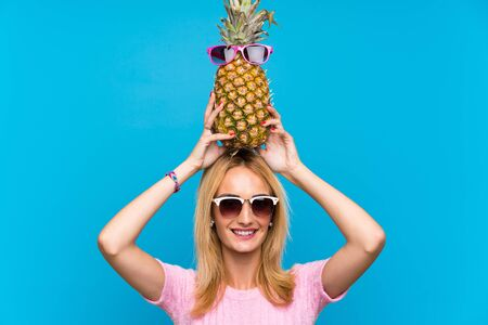 Young woman holding a  pineapple with sunglasses