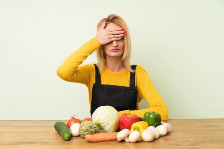 Joven mujer rubia con muchas verduras que cubren los ojos con las manos