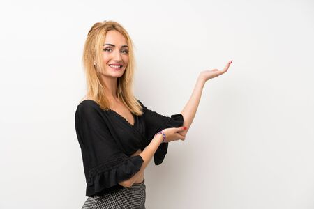 Young blonde woman over isolated white wall extending hands to the side for inviting to come Banco de Imagens
