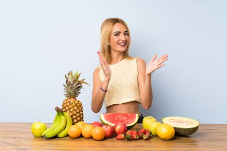 Young blonde woman with lots of fruits applauding Stock fotó