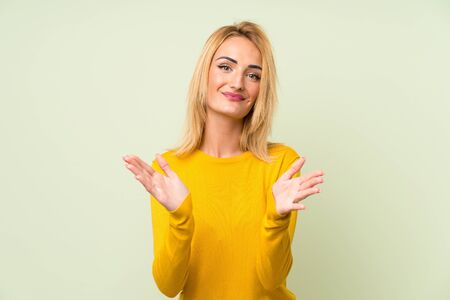 Young blonde woman over isolated green background applauding Stock fotó