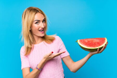 Happy Young blonde woman holding fruits