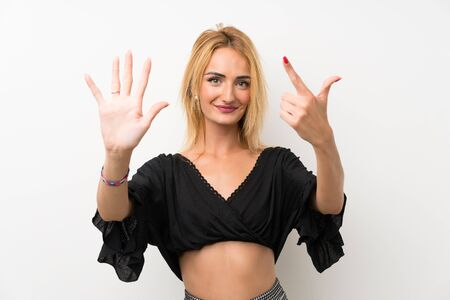 Young blonde woman over isolated white wall counting seven with fingers