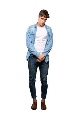 Una foto a figura intera di un bel giovane con espressione triste e depressa su sfondo bianco isolato