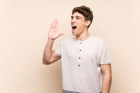 Handsome young man over isolated background shouting with mouth wide open