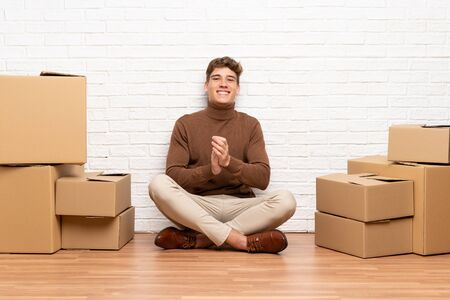 Handsome young man moving in new home among boxes applauding